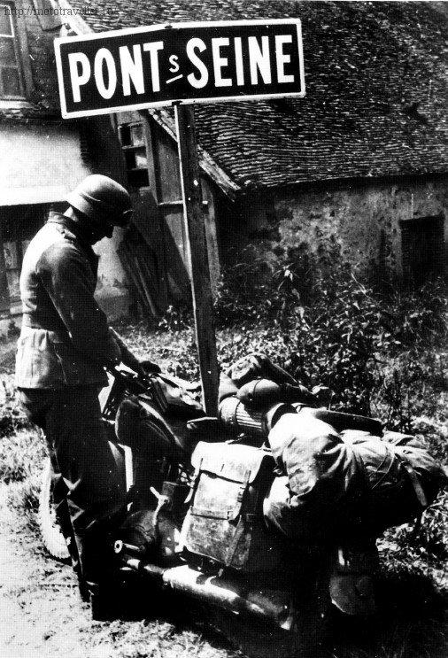 Военный мотоциклист Вермахта рядом с указателем