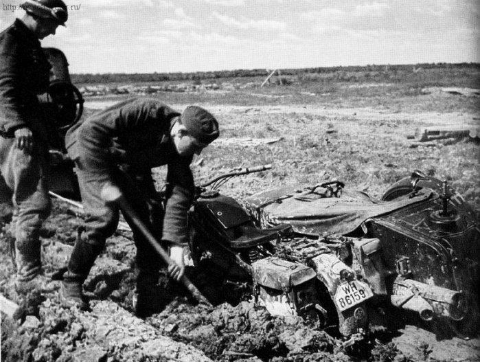 Солдаты откапывают из грязи военный мотоцикл